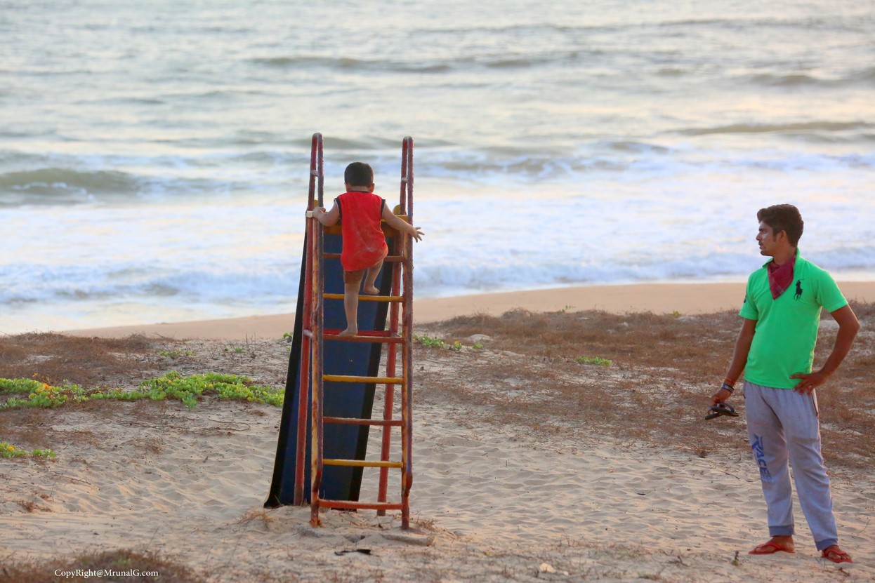 A father watches his son play at the Mithmubari beach slide.