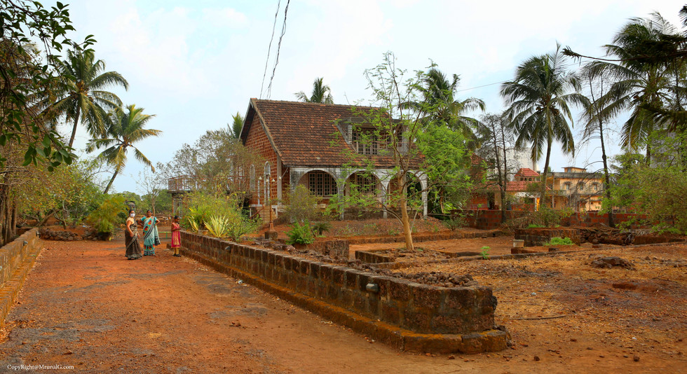 A villa type old house with big area with trees around it.