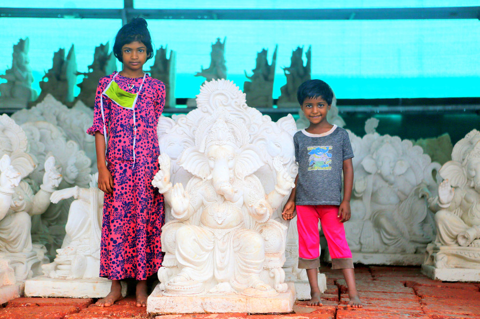 Children pose along with Ganesha idols soon to be colored for the Ganesha festival in Aug.