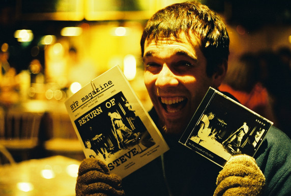 STEVE bassist Nick holding his copies of HỲP Magazine and IN THE EVENT OF RHYTHM