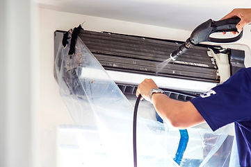 The technicians are cleaning the air conditioner by spraying water. Hand and water spray a