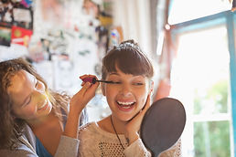 Young girls putting on makeup