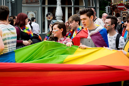 Parade marchers carrying a pride flag