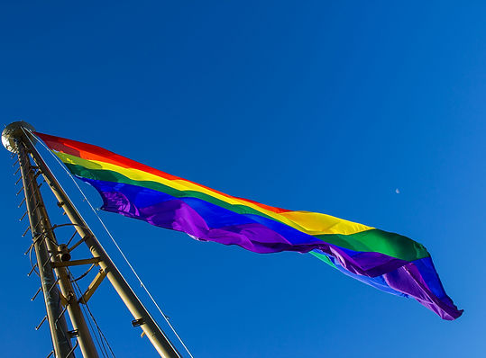 Pride flag waving against a clear blue sky