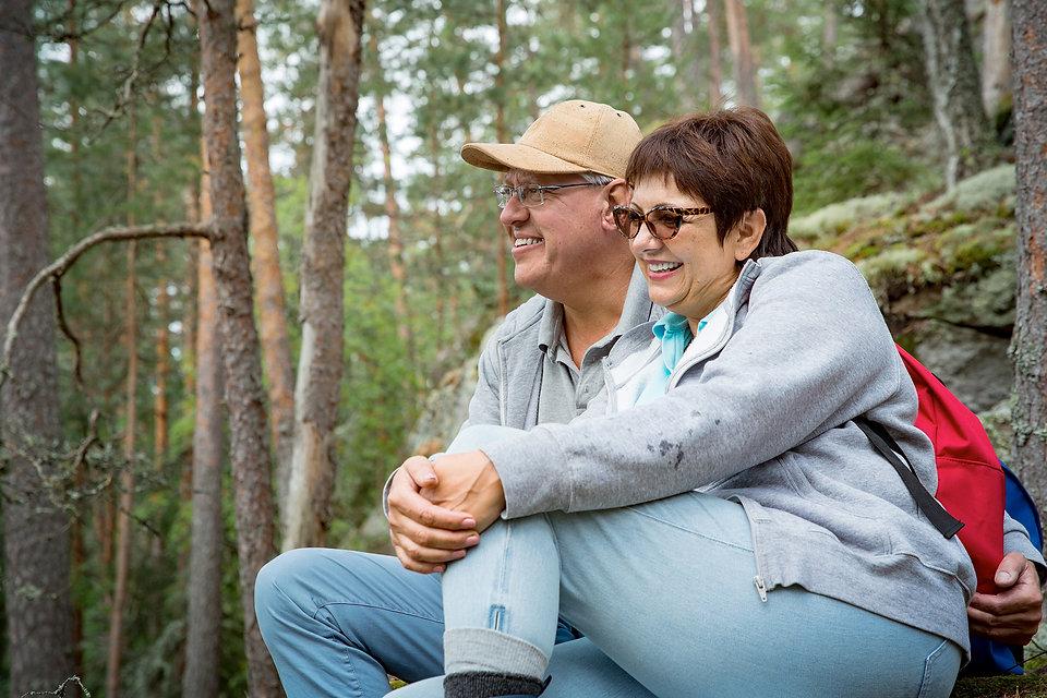 Pariskunta istuskelemassa luonnossa.