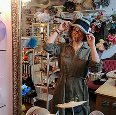 A woman tries a hat on the mirror of a hat shop.