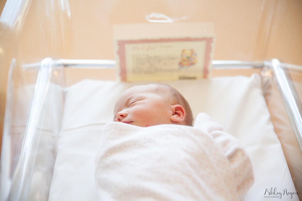 swaddled newborn in bassinet