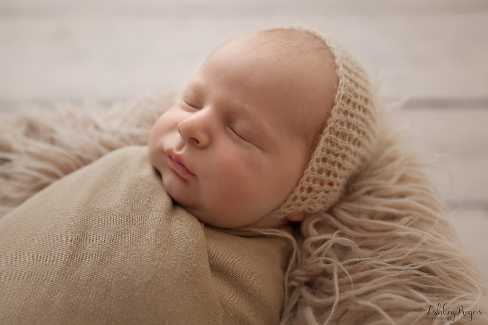 newborn wearing a bonnet