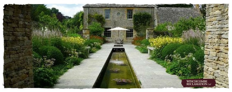 a long rill of still water running to a seating area outside a beautiful Cotswold house