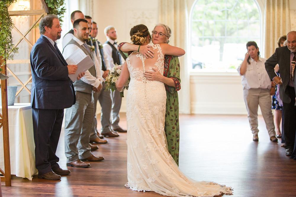 mother handing off daughter wedding