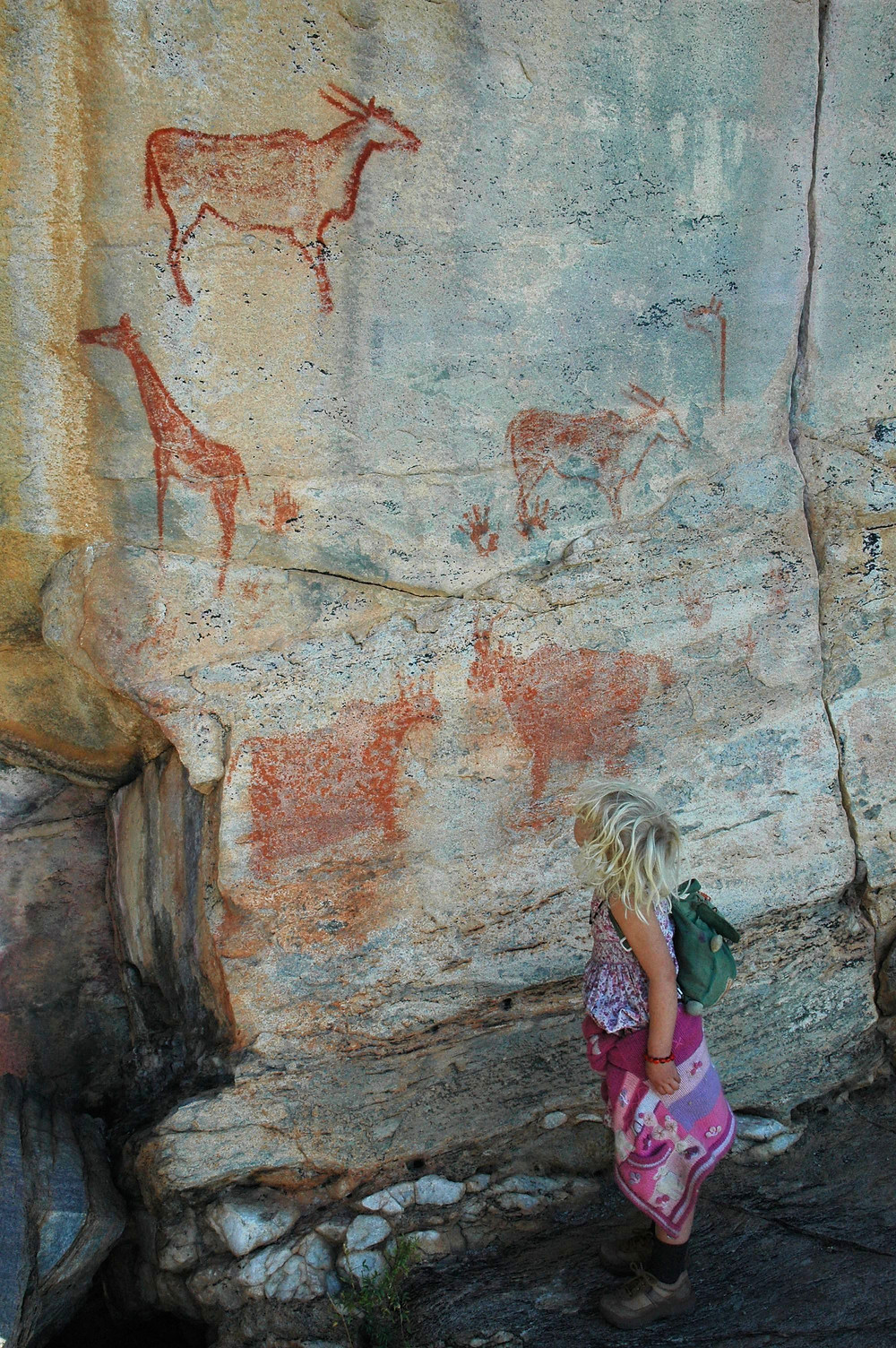 My daughter, then 4 years old, stands by a group of paintings, showing an eland at the top, a giraffe on the left, and, if you look closely, a handprint in the middle, Tsodilo Hills. Photo: Jessica Groenendijk