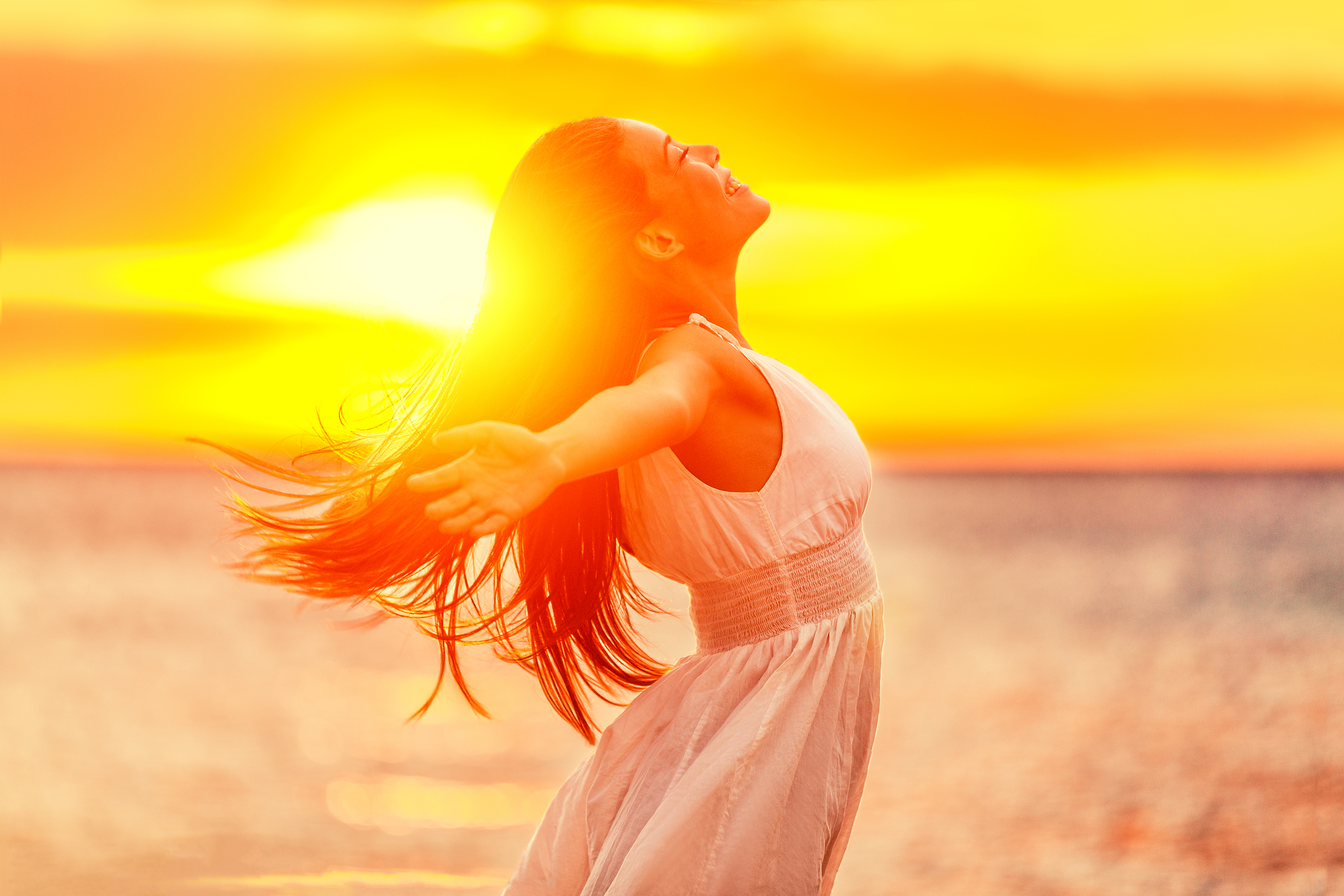 Happy woman feeling free with open arms in sunshine at beach sunset. Freedom and carefree enjoyment