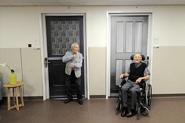 Two older gentlemen in front of their True Doors in long term care home