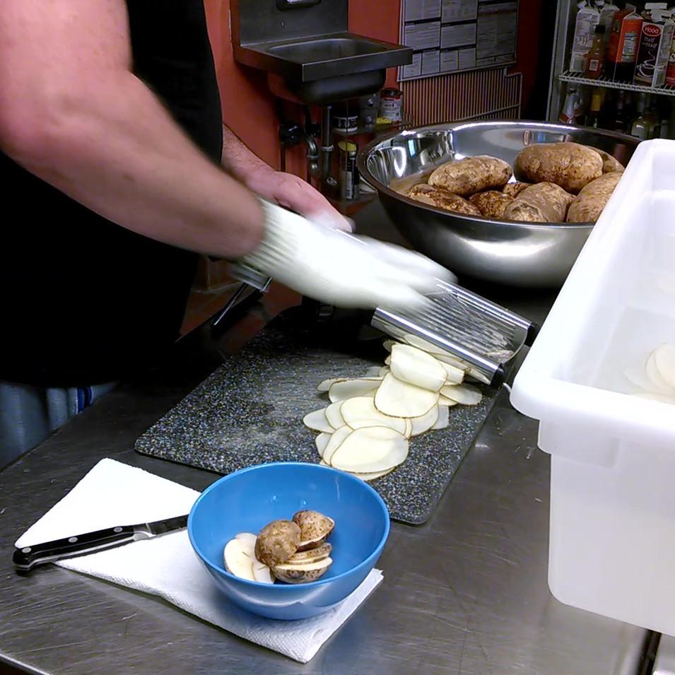 Hand slicing potatoes