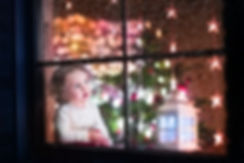 Memories that last a lifetime. Little child watching in wonder with lit christmas tree.