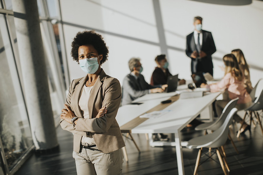 Employees in a meeting wearing face coverings