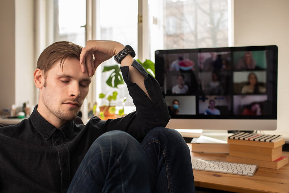 Man Fatigue during home video conference meeting call. Post-work exhaustion from constant face-to-face digital interactions. Working remotely Stay connected during pandemic to combat lonelines