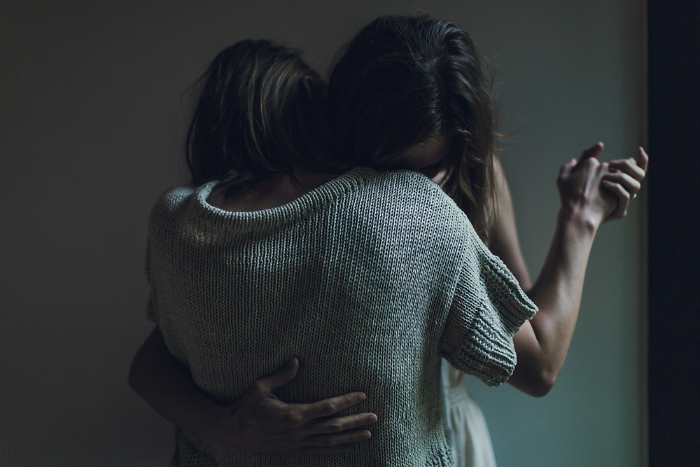 Two women are slow dancing in a room. One rests her head on the other woman's shoulders.