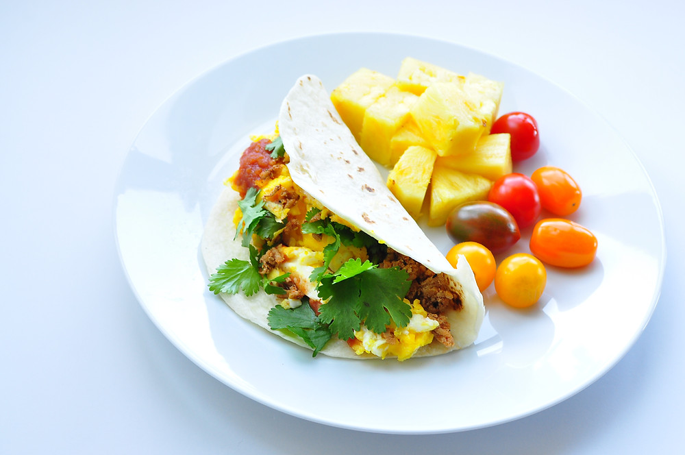 A white flour tortilla is folded in half and filled with scrambled eggs, ground turkey, salsa and cilantro to create a breakfast taco. Pineapple and cherry tomatoes sit on the plate next to the breakfast taco.