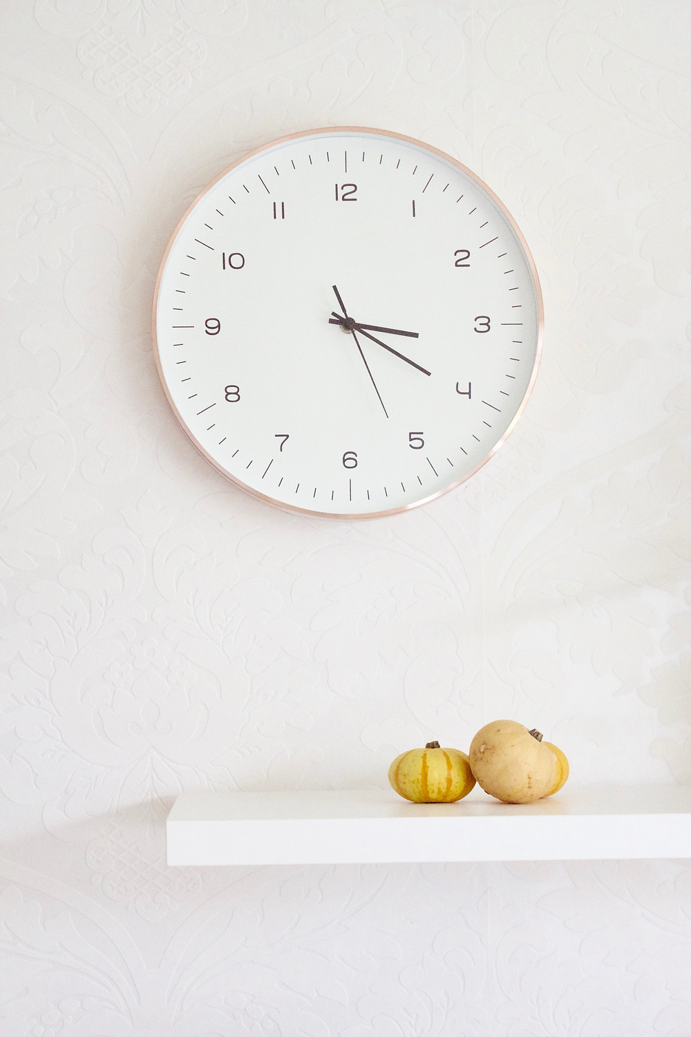 A white clock is on a white wall above a white shelf with two yellow gourds sitting in it