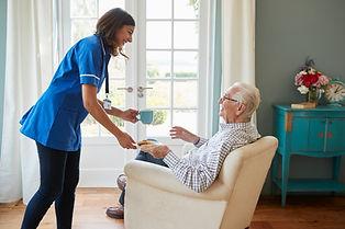 nurse-serving-a-cup-of-tea-to-a-senior-m