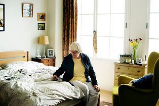 senior-woman-sitting-on-the-bed-SRB4C95.