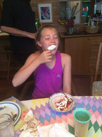 Niece Myah eating strawberries over pie crust with whipped cream