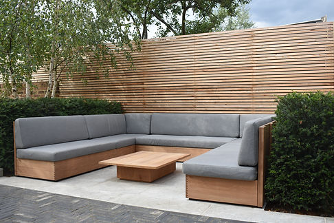 Studio Cullis contemporary bespoke built-in timber wooden seating within a modern London garden design wth perennials fabric cushions and bespoke timber gaden table