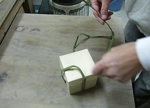 Some of Iinuma's sake cups come with a traditional wooden box. The special method of tying the bow is shown in the video above.