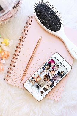 pink note book with phone showing social media