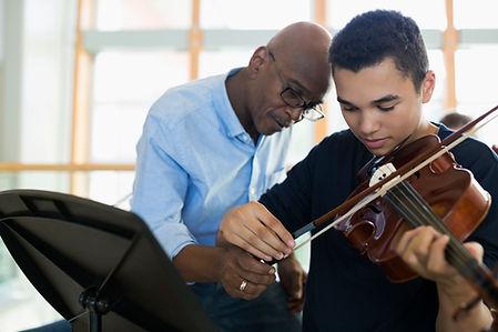 Leraar helpt student viool te spelen