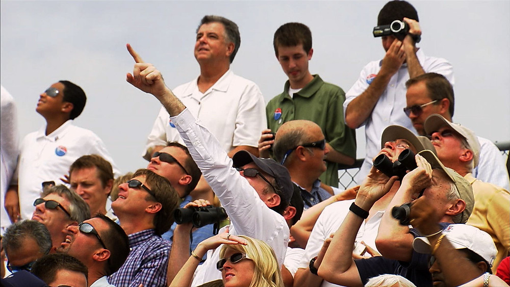 Crowds watch the space shuttle take off.