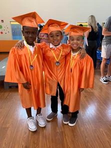 Three kids graduating Pre-Kindergarten in the indoor gym