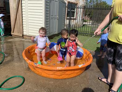 One year olds enjoying splash day at the school's playground