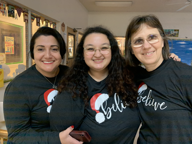 Preschool owner and infant classroom teachers taking photo with matching winter shirts
