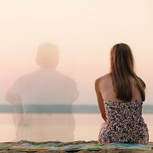 Rear view of semi-transparent man and woman in summer dress sitting on beach towel looking at sea on