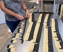 Black and yellow cut pasta seperated by hand