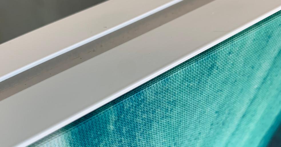 Akustisk skærmvæg med hvid ramme (der er spor i rammen til at montere fødder)