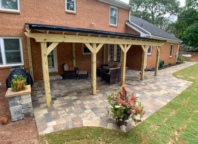 Pine pergola with metal roof on top of a paver patio