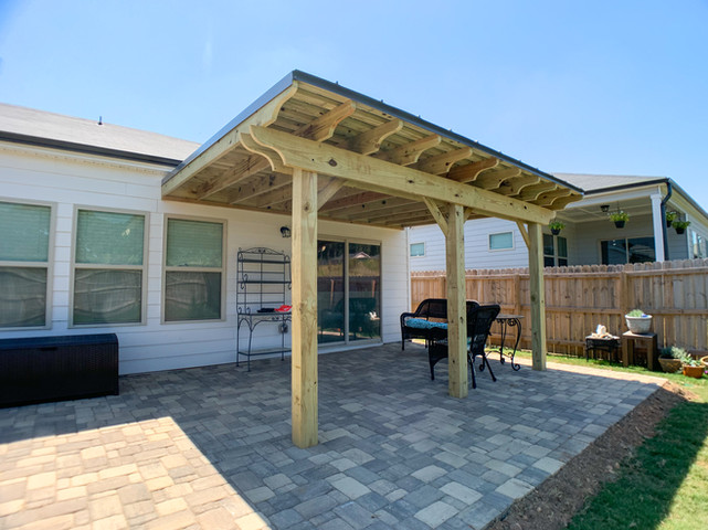 Pine pergola with metal roof on top of paver patio