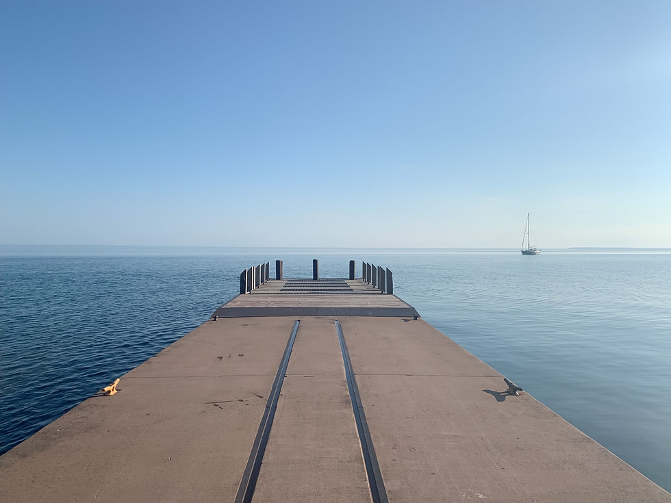 Dock in lake superior with sailboat in the distance