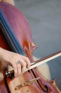 אישה מחזיקה קשת ומנגנת על צ'לו לכן יש לה כישרון מוזיקלי
