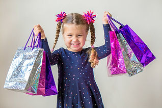 Smiling little girl with shopping bags w