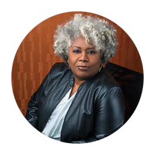 Faculty headshot of Anthea Butler. Anthea is a Black woman seated in a black chair looking into the camera. She is wearing a black leather jacket with a grey top and has short, curly black and white hair.