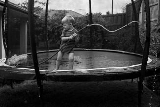 boy on trampoline with hose
