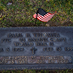 Memorial grave-plaque of Paul Thomer states his historical affiliation with the U.S. Marine Corps as a private first class during World War II on Veterans day on Nov. 11, 2020, in the San Fernando Mission Catholic Cemetery on 11160 Stranwood Ave. in Mission Hills, Calif. Thomer's plaque also pays respect to his loved one Frances Thomer. The plaque is decorated with an American flag.