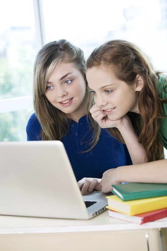 Happy teen students with computer