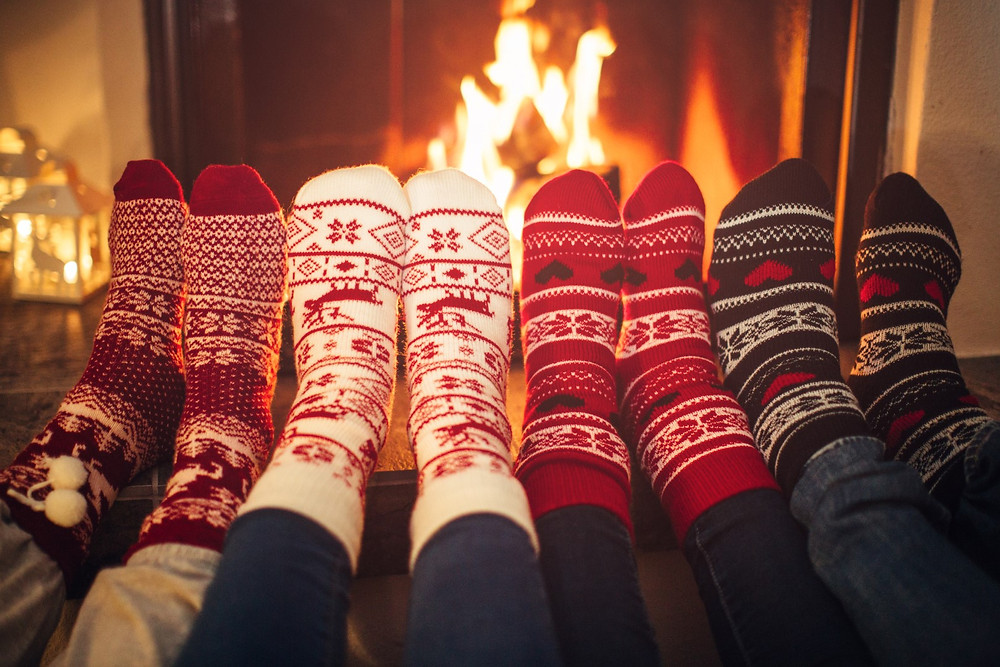 Four pairs of feet with holiday socks in front of a fireplace