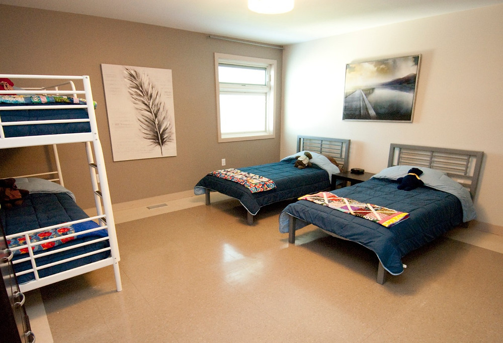 IHO bedroom with 2 single beds, 1 bunk bed, and pictures on walls