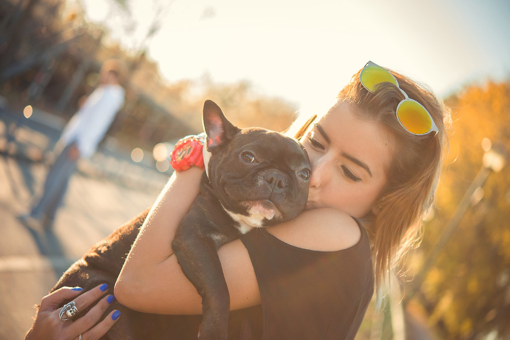 Woman in sunshine holding and kissing small black dog